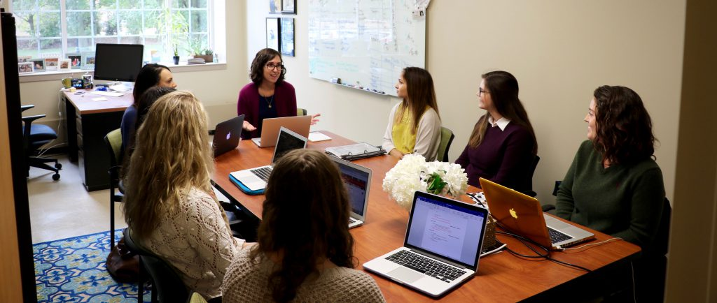Student and faculty researchers hold a laboratory meeting to discuss research projects.