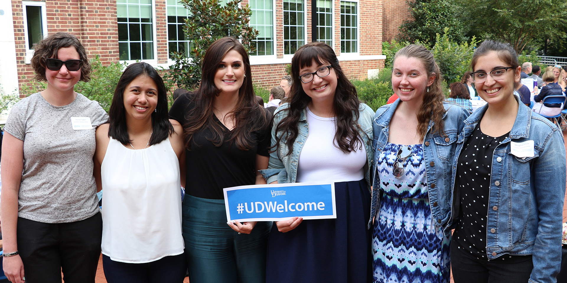 Graduate students holding UD Welcome sign