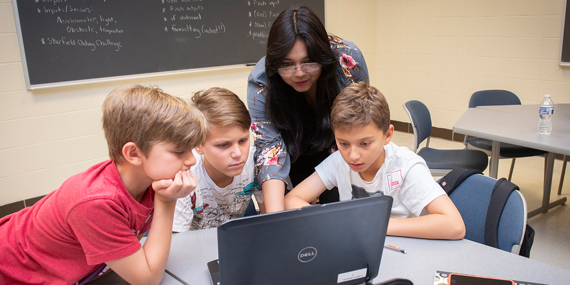 Teacher helping students with computer assignment