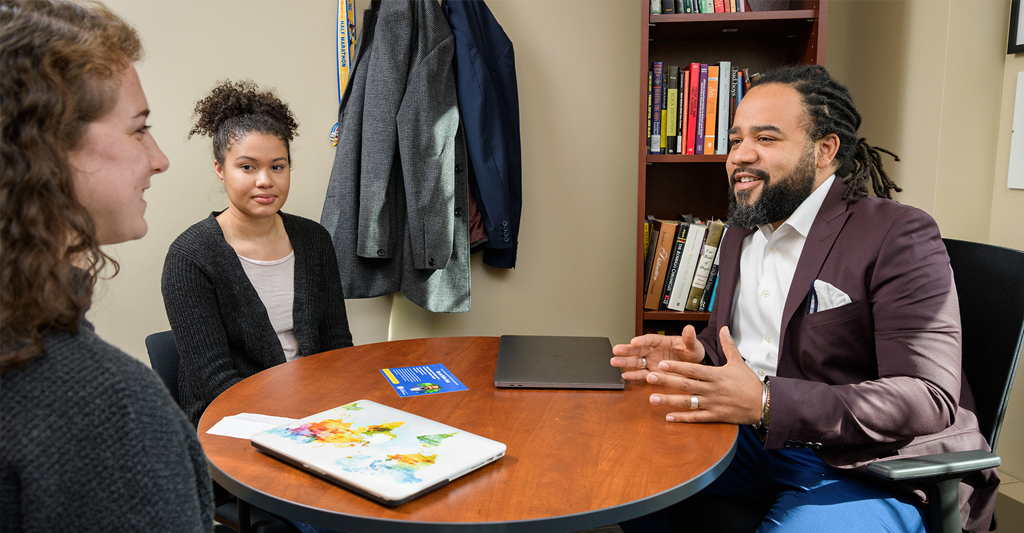 Dr. Roderick Carey speaks with two students